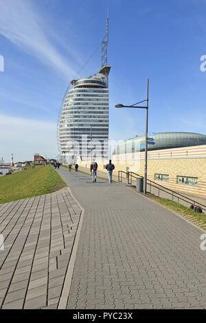 Dyke and promenade by the river Weser with the conspicuously Atlantic Hotel Sail City in Bremerhaven in front of blue sky, 6 April 2018 | usage worldwide - Stock Photo