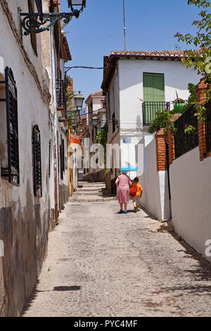 Woman & boy walking up cobbled street with parasol in old town of Granada - Stock Photo