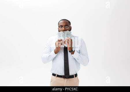 young cheerful black businessman holding cash on his face at money isolated on white - Stock Photo
