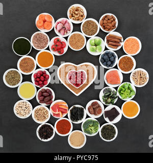 Superfood to slow the ageing process including fruit, vegetables, herbs, spices, fruit, fish, supplement powders, seeds and nuts on slate. Very high i - Stock Photo