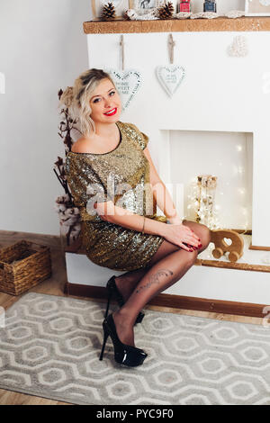 Beautiful smiling woman in bright golden dress sitting at fireplace. - Stock Photo