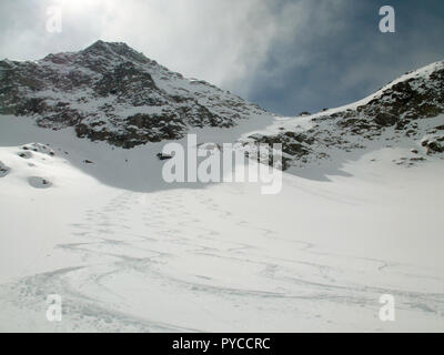 picturesque deep winter mountain landscape in the Alps of Switzerland with backcountry ski tracks in fresh powder - Stock Photo