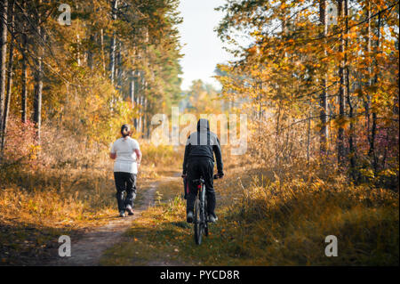 A young woman runs through the woods. The coach is riding a Bicycle nearby. The concept of a healthy lifestyle and weight management. - Stock Photo