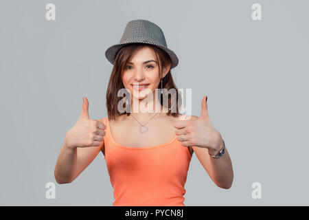 Happy smiling woman with gray hat showing thumbs up like gesture isolated grey studio wall background. Positive emotion face expression sign symbol bo - Stock Photo