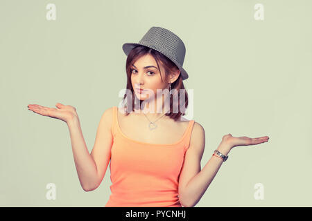 Closeup portrait of pretty angry unhappy young woman with arms out asking what's the problem who cares so what. Isolated on light green yellow backgro - Stock Photo