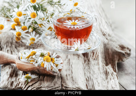 A clear Cup of medicinal chamomile tea on an old wooden table. Health and healthy lifestyle concept. - Stock Photo