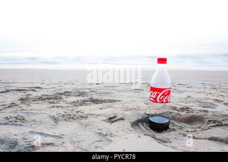 Kochi, Kerala, India - January 11, 2015: Almost empty plastic Coca Cola bottle left on a footprint in the sand on Arabian sea beach in Kochi. - Stock Photo