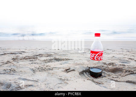 Kochi, Kerala, India - January 11, 2015: Almost empty plastic Coca Cola bottle left on a footprint in the sand on Arabian sea beach in Kochi. - Stock Photo
