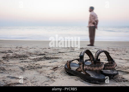 Kochi, Kerala, India - January 11, 2015: Long exposure shot of the sandals 'Source' on the sand beach of Arabian sea at the sunset in Kochi together w - Stock Photo