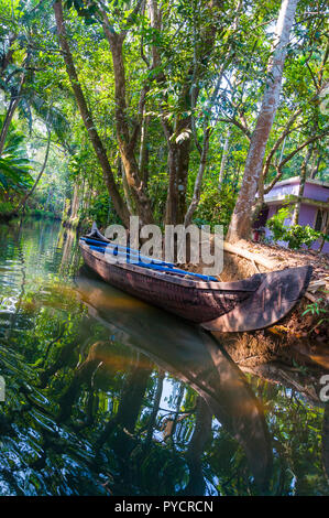 Traditional boat of Kerala Backwaters moored to the shore. Backwaters in Kerala is a network of 1500 km of canals both man made and natural. - Stock Photo