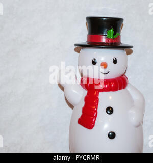 Toy snowman waving with white scarf and black top hat with red sash. There is a white background. - Stock Photo