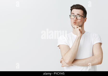 Guy checking out something cool whistling from impression and amazement expressing surprise and delight folding lips holding hands on chin at raising eyebrow from surprise and interest - Stock Photo