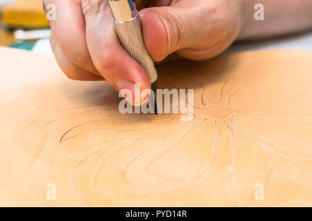 workshop of making the carved leather bag - craftsman carves ornament on surface of rough vegetable tanned leather by swivel knife - Stock Photo