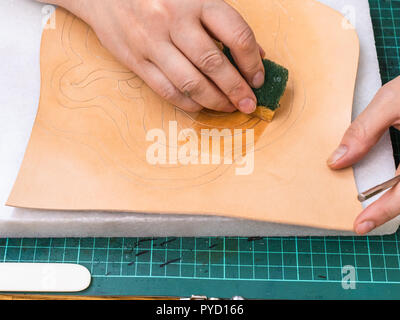 workshop of making the carved leather bag - craftsman dampens the pattern on surface of rough vegetable tanned leather before stamping - Stock Photo