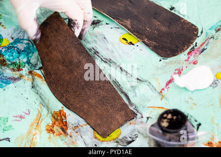 workshop of making the carved leather bag - craftsman stains the carved leather items of handbag - Stock Photo