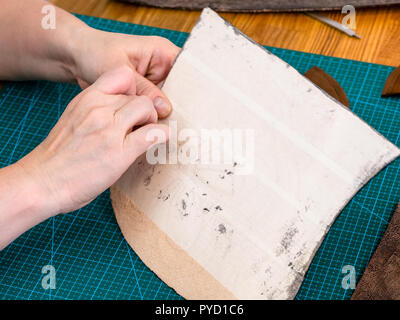 workshop of making the carved leather bag - craftsman removes the protective fabric from the back side of leather item of the handbag - Stock Photo