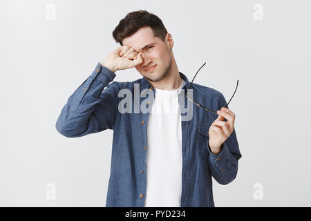 Waist-up shot of tired male freelancer taking of glasses as working long near computer on gig economy project rubbing eye and frowning being exhausted standing drained and upset over grey wall - Stock Photo