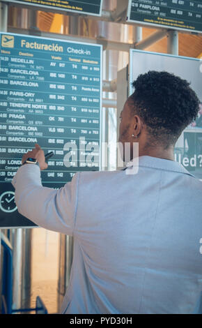 One young and attractive black businessman is looking for his flight to Barcelona in the airport terminal near check-in screens. He is wearing formal  - Stock Photo
