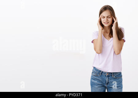 Put your mind together. Portrait of intense cute european girl with brown hair closing eyes holding hands on temples of head trying focus and concentrate, standing unfocused over grey wall - Stock Photo