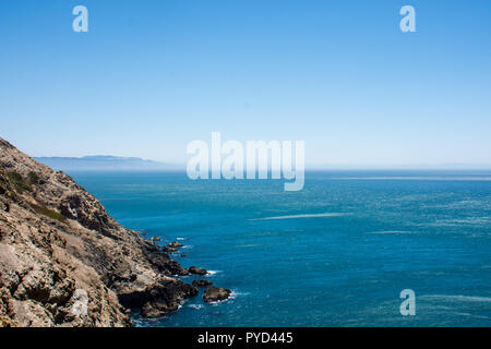 Oceanside cliffs at Point Reyes National Seashore in Marin County, California. Bright blue color of the Pacific Ocean, on a sunny day, with extra copy - Stock Photo