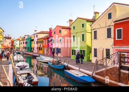 Burano, Italy - October 2018: Tourists walking around the colorful fishermen's houses in Burano - Stock Photo