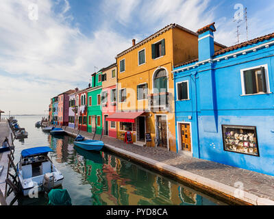 Burano, Italy - October 2018: A view of the colorful fishermen's houses in Burano on a clear day - Stock Photo