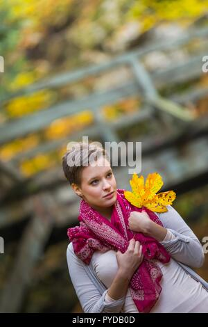 Stunning short-haired teen teengirl girl isolated in nature holding big Yellow Autumn season leaf looking away at distance - Stock Photo