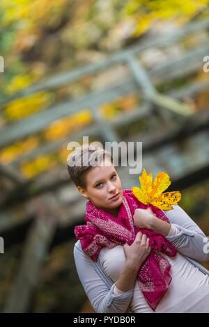 Short-haired teen girl isolated in nature holding big Yellow Autumn season leaf looking at camera wearing Red scarf - Stock Photo