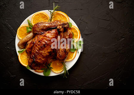 Roasted whole chicken or turkey served in white ceramic plate with oranges and lamb's lettuce on dark stone background. View from above. - Stock Photo