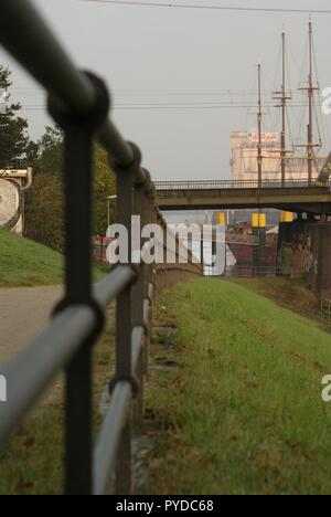 Pedestrian fence in Bremen Weser with view on ocean ship sailing with gras in behind - Stock Photo