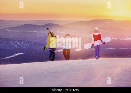 Three friends skiers and snowboarders are walking on mountain top at sunset - Stock Photo