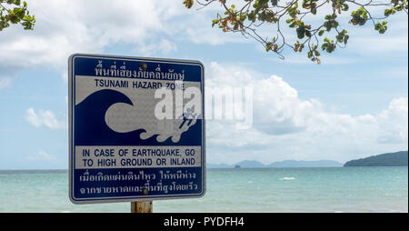Tsunami Hazard zone sign with beach and islands in the background - Stock Photo