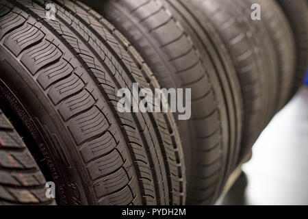 New black car tire, closeup.Brand new winter tires with a modern tread isolated.selective focus.Tire stack background.Winter season. Texture of car tire tread. - Stock Photo