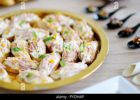 Delicious tuna mini sandwiches decorated with basil served on a party or wedding reception. Plates with assorted fancy finger food snacks on an event  - Stock Photo