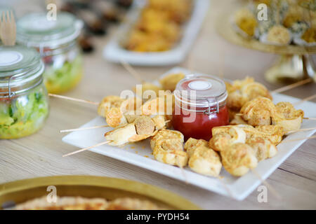 Fresh and delicious chicken and cheese skewers served with sauce in a jar ion a party or wedding reception. Plates with assorted fancy finger food sna - Stock Photo