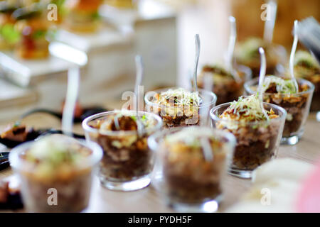 Fresh and delicious vegetable and pork salad served in mini glasses on a party or wedding reception. Plates with assorted fancy finger food snacks on  - Stock Photo