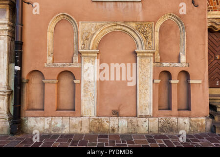 Arched niches od different size on St Barbara's Church wall in Old Town of Krakow in Poland. - Stock Photo