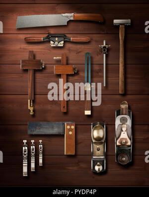 Precision carpentry tools hanging on a wooden panelled wall - Stock Photo