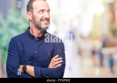 Middle age hoary senior man over isolated background smiling looking side and staring away thinking.