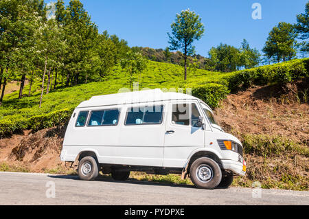 Munnar, Kerala, India - January 14, 2015: The white minibus Mercedes Benz parked on hairpin turn road surrounded by a tea plantations of Munnar mounta - Stock Photo