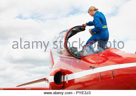 Red Arrows pilot entering cockpit on RAF Scrampton, UK - Stock Photo