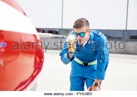 Mechanic looking at airplane propeller with torch on RAF Scrampton, UK - Stock Photo