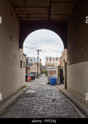 Looking down an Old Passageway with a cobbled road surface on a Cloudy Summers day in Glasgow, Scotland, UK. - Stock Photo