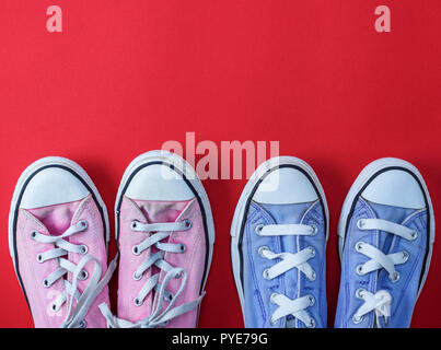 two pairs of worn textile sneakers with white laces on a red background, top view, copy space - Stock Photo