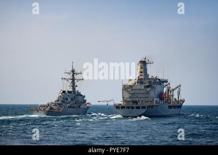 181023-N-UX013-1004 ARABIAN GULF (Oct. 23, 2018) The guided-missile destroyer USS Decatur (DDG 73), left, conducts a replenishment-at-sea with the fleet replenishment oiler USNS Kanawah (T-AO 196). Decatur is deployed to the U.S. 5th Fleet area of operations in support of naval operations to ensure maritime stability and security in the Central Region, connecting the Mediterranean and the Pacific through the western Indian Ocean and three strategic choke points. (U.S. Navy photo by Mass Communication Specialists 3rd Class Jonathan Clay/Released) - Stock Photo
