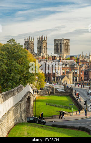 Scenic autumn York cityscape - historic landmarks, medieval walls, sunlit Minster towers, Lendal Bridge & people walking - North Yorkshire, England UK