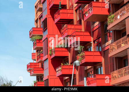 Facade of a modern red apartment house with many balconies seen in Berlin, Germany - Stock Photo