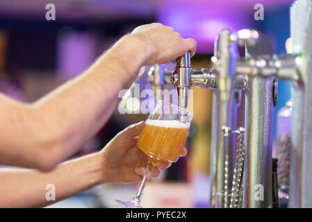Barman in the pub pouring a lager beer in a glass, shallow dof, selective focus. - Stock Photo