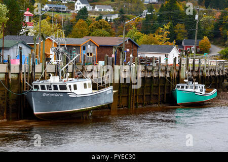 East coast fishing boats moored to the dock at low tide in the village of Saint Martins New Brunswick Canada - Stock Photo
