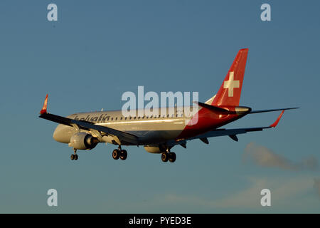 Helvetic Airways Embraer ERJ-190LR landing at London City Airport at  sunset - Stock Photo